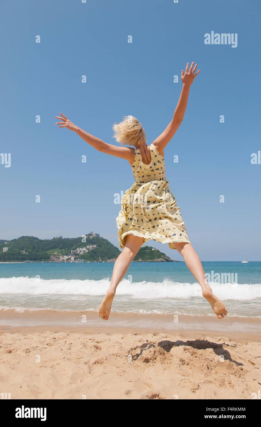 Mujer saltando en la playa, mirando a la bahía de Vizcaya - Bizkaia, Gipuzkoa, San Sebastián Imagen De Stock