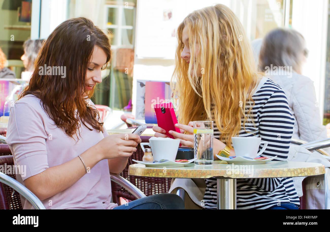 Mujer joven con dos nuevos teléfonos inteligentes. Imagen De Stock