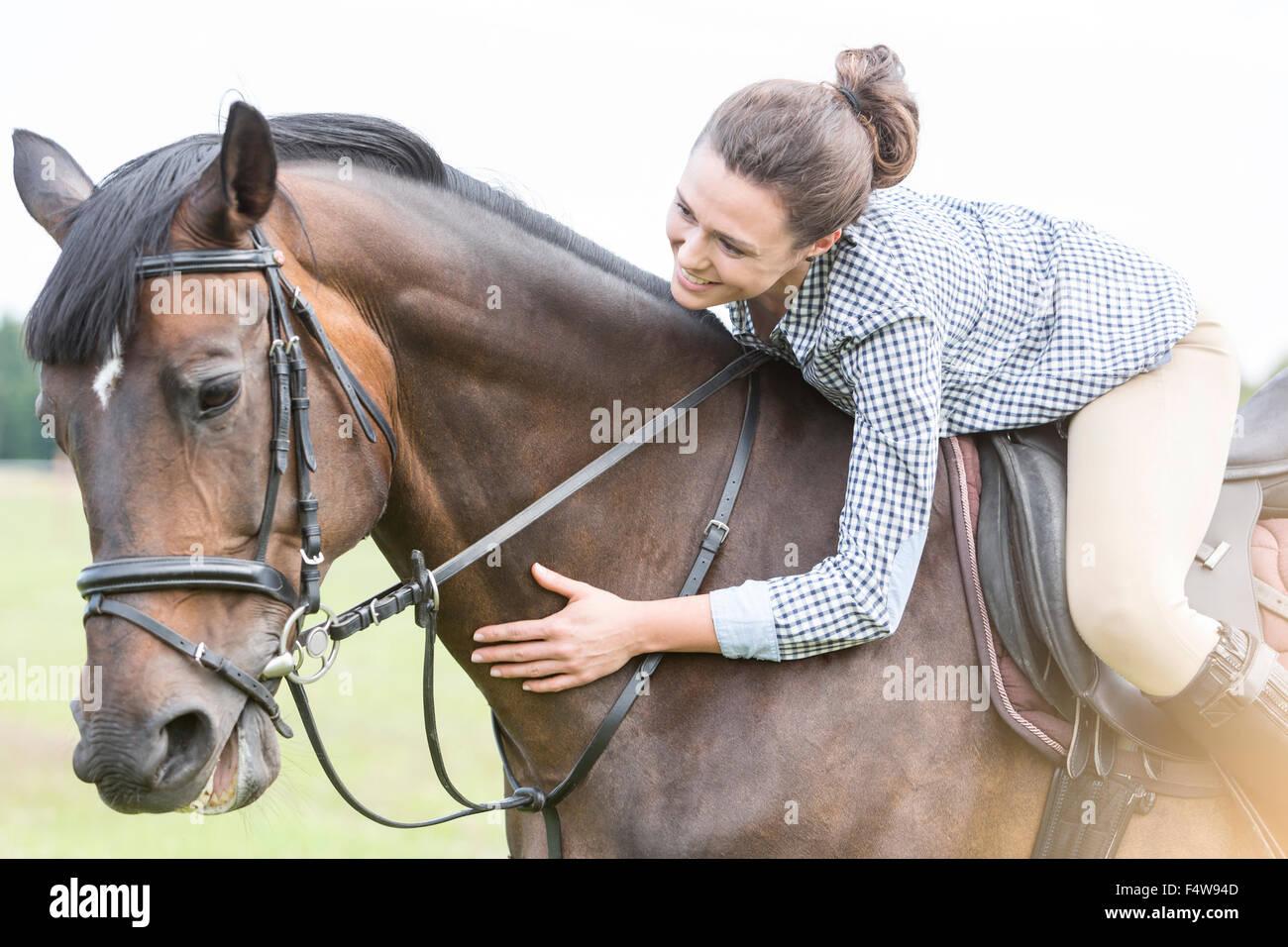 Mujer sonriente montar a caballo del caballo y besándose inclinada Imagen De Stock