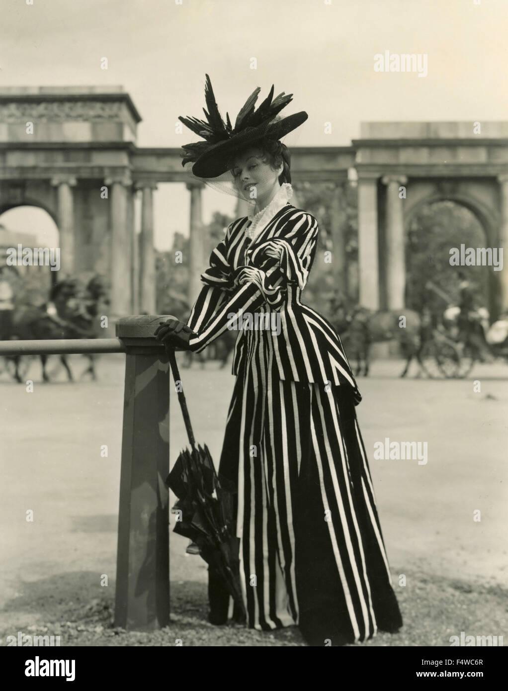 Una modelo presenta un vestido estilo 1800 en rayas blancas y negras Imagen De Stock