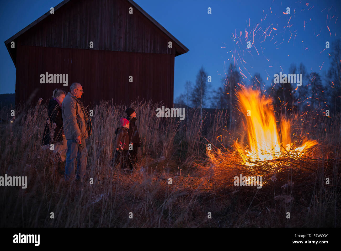 Suecia, Narke, Filipshyttan, abuelo con los nietos (6-7,8-9,16-17) mirando fogata Imagen De Stock