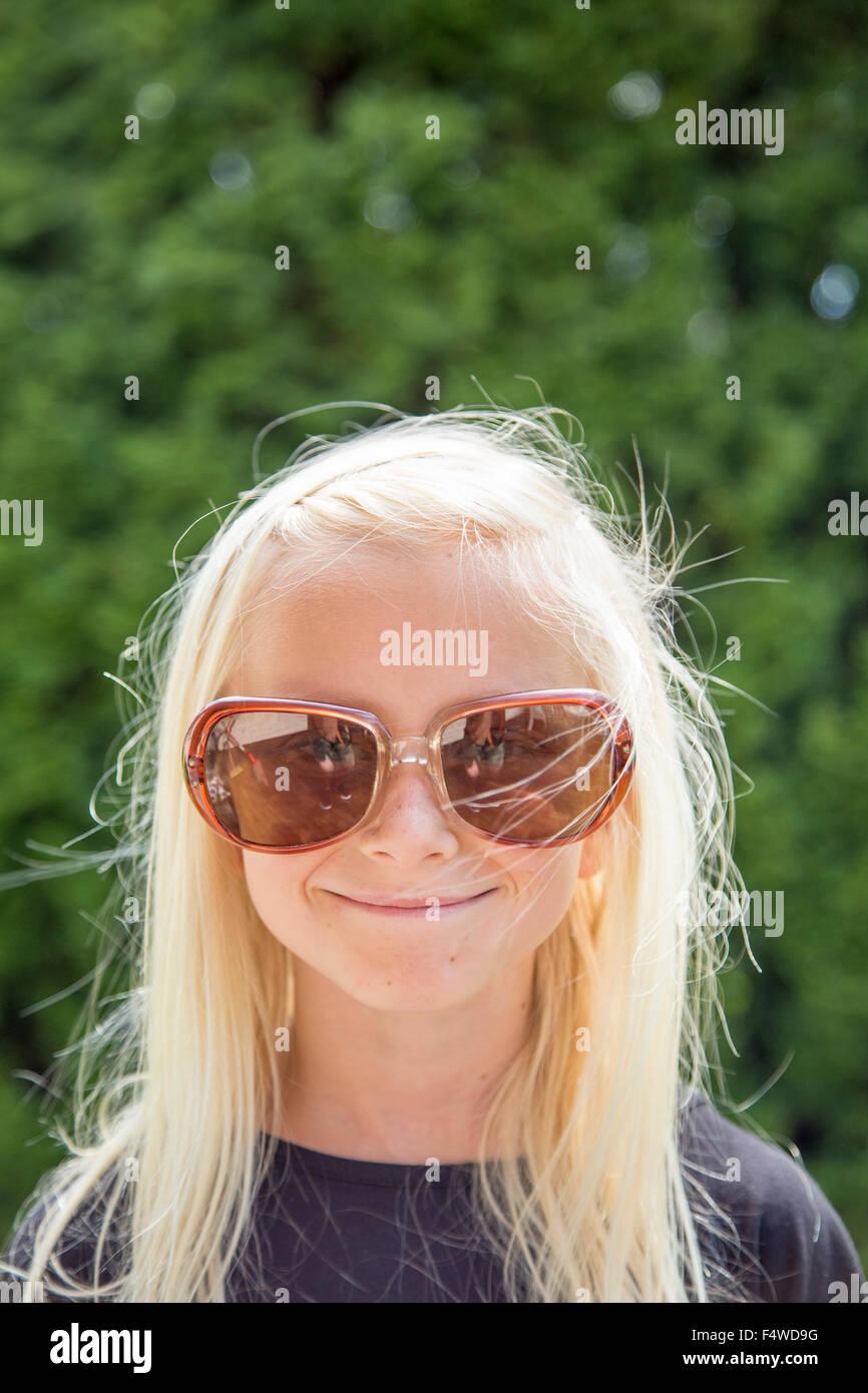 Suecia, Smaland, Anderstorp, Retrato de niña (10-11) llevando gafas de sol grande Imagen De Stock