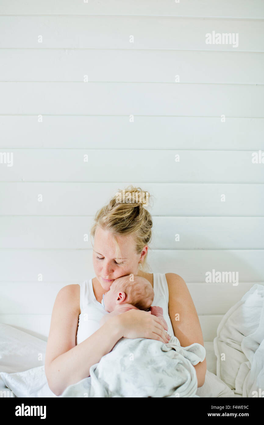 Mujer adulta media holding Baby Boy (0-1 meses) en sus brazos Imagen De Stock