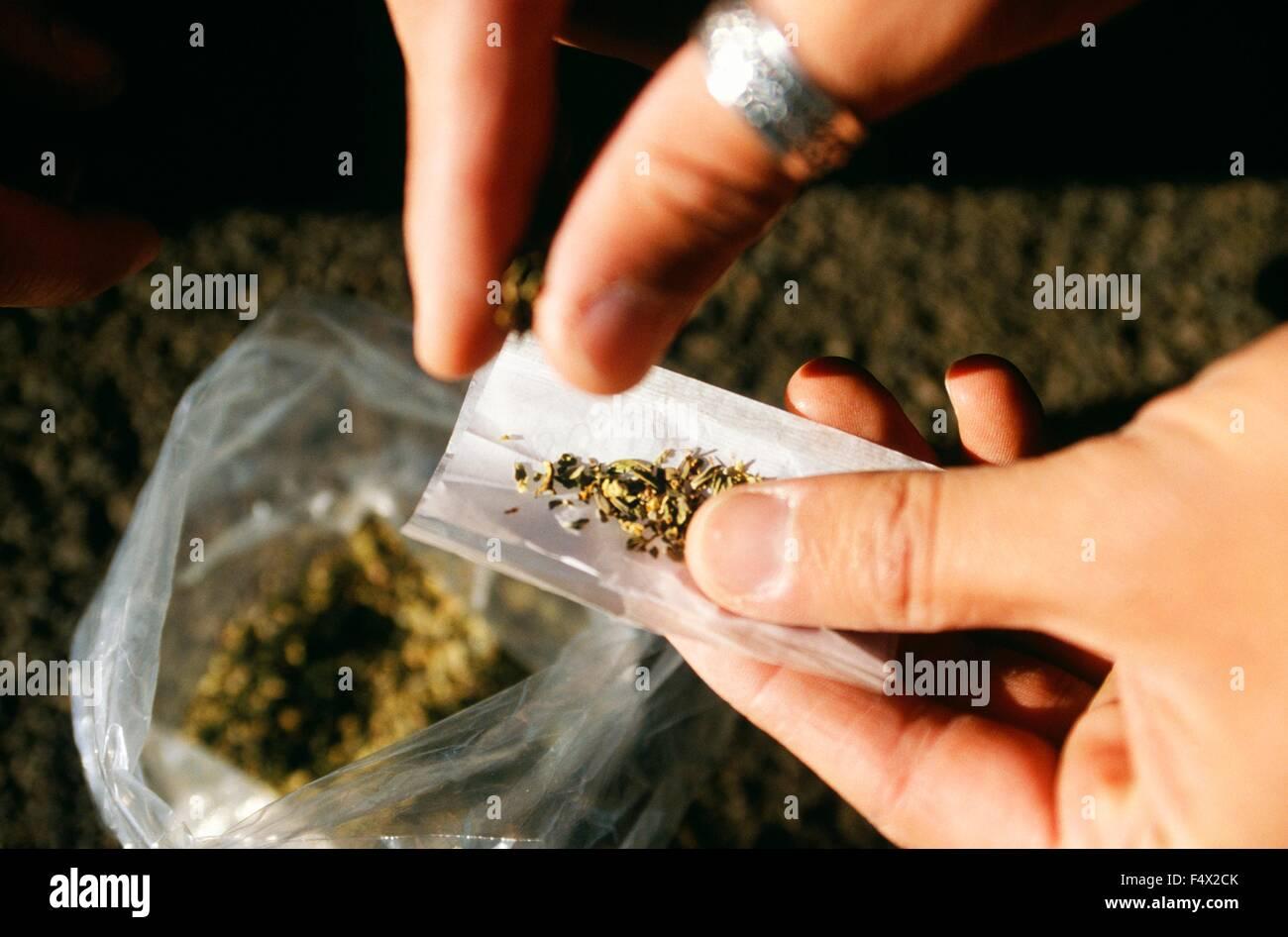 Un toxicómano rollos una articulación utilizando un cannabinoide sintético llamado Spice utilizar Imagen De Stock