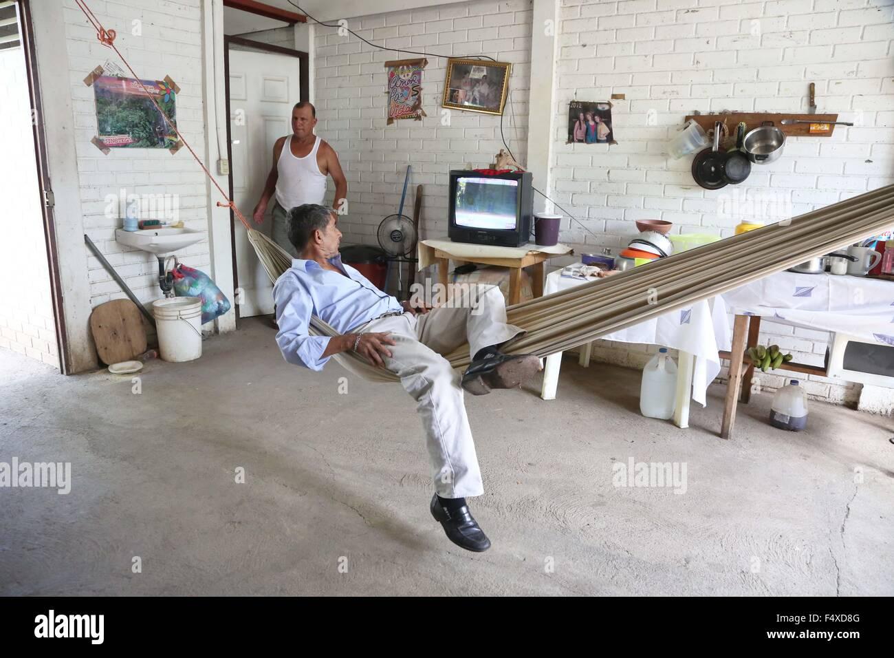 """Managua. 22 Oct, 2015. Imagen tomada en el pasado 22 de octubre, 2015 muestra José Castillo (delantero) descansando en una hamaca en su casa en la ciudadela """"héroes y mártires de nemagón"""" en Managua, Nicaragua. La ciudadela """"héroes y mártires de nemagón"""" fue beneficiado por las """"Casas para el pueblo"""", un programa, implementado desde 2007 y consiste en la construcción y la prestación de servicios sociales a la población de los hogares en situación de pobreza que viven en las zonas rurales y urbanas. © Juan Bustos/Xinhua/Alamy Live News Foto de stock"""