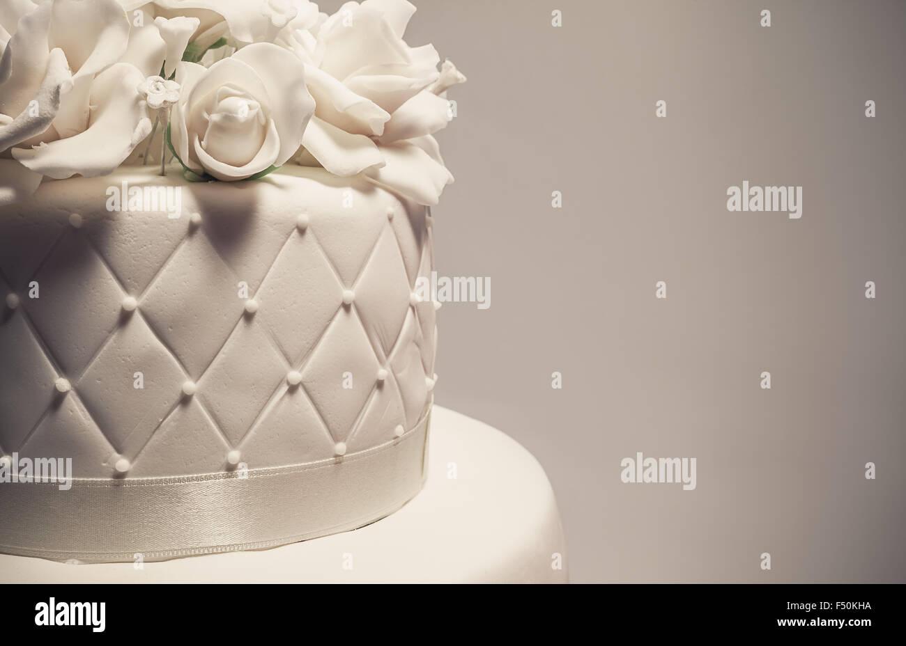 Detalles de un pastel de bodas, decoración con fondant blanco sobre fondo blanco. Imagen De Stock