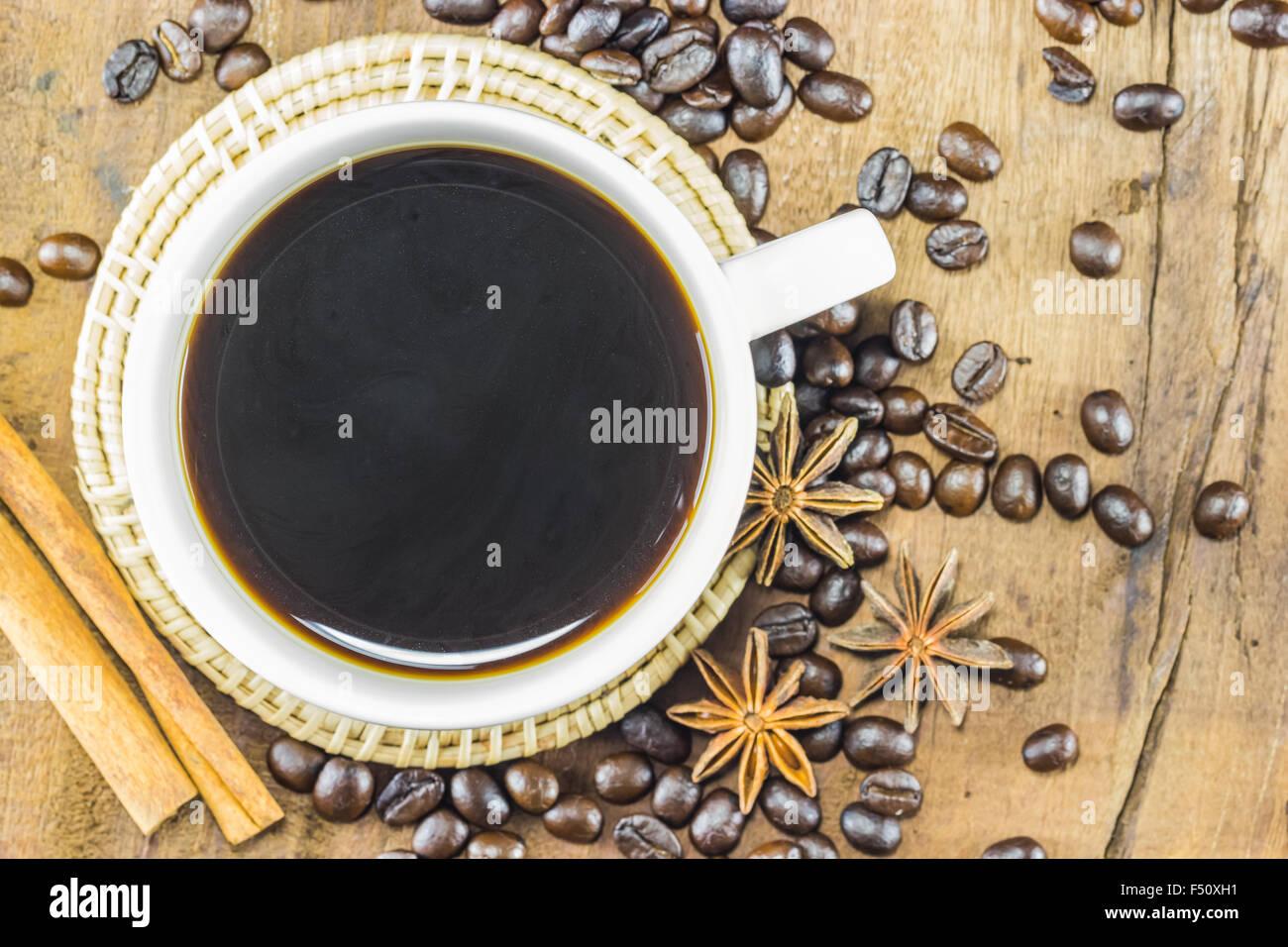 En la taza de café con granos de café y Canela palos de madera, cálidos tonos de fondo, el enfoque Imagen De Stock