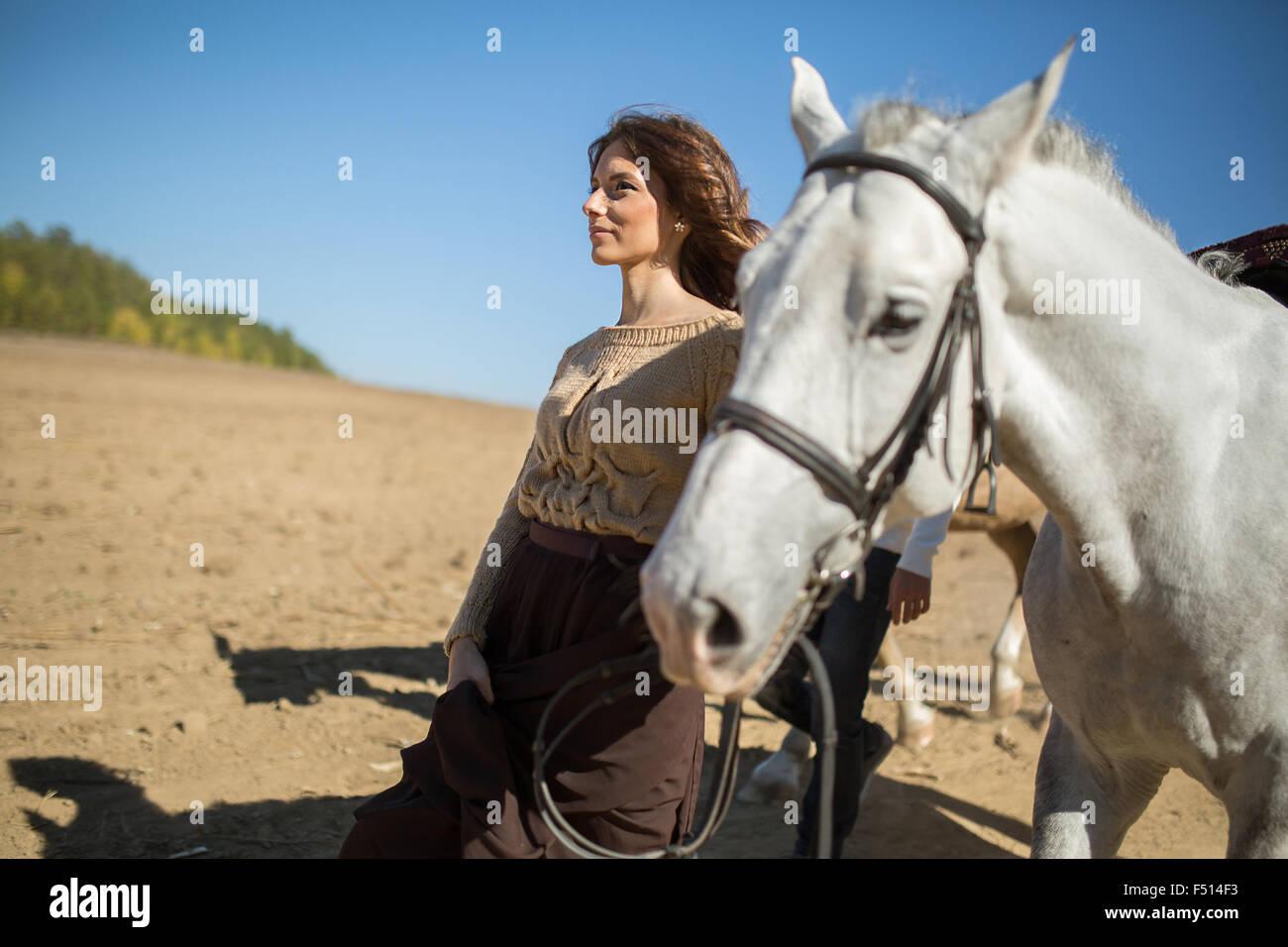 Atractiva chica joven está caminando con su caballo Foto de stock