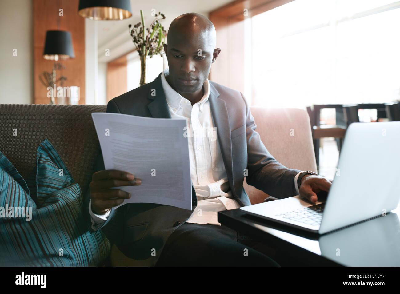 Imagen del joven empresario sentado a la cafetería del hotel leyendo un documento mientras trabaja en una computadora Imagen De Stock