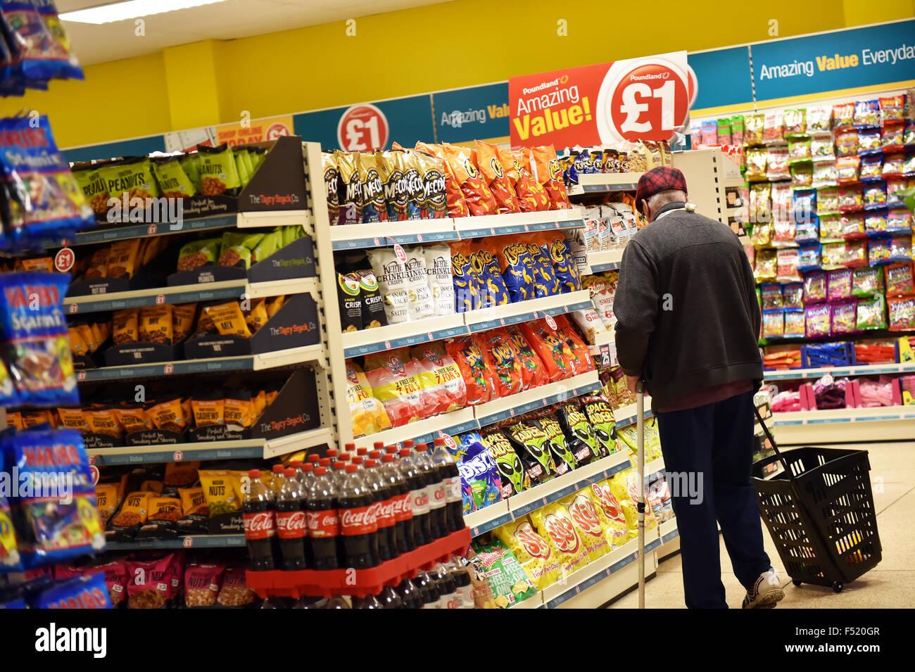 Un pensionista tiendas en un almacén Poundland UK Imagen De Stock