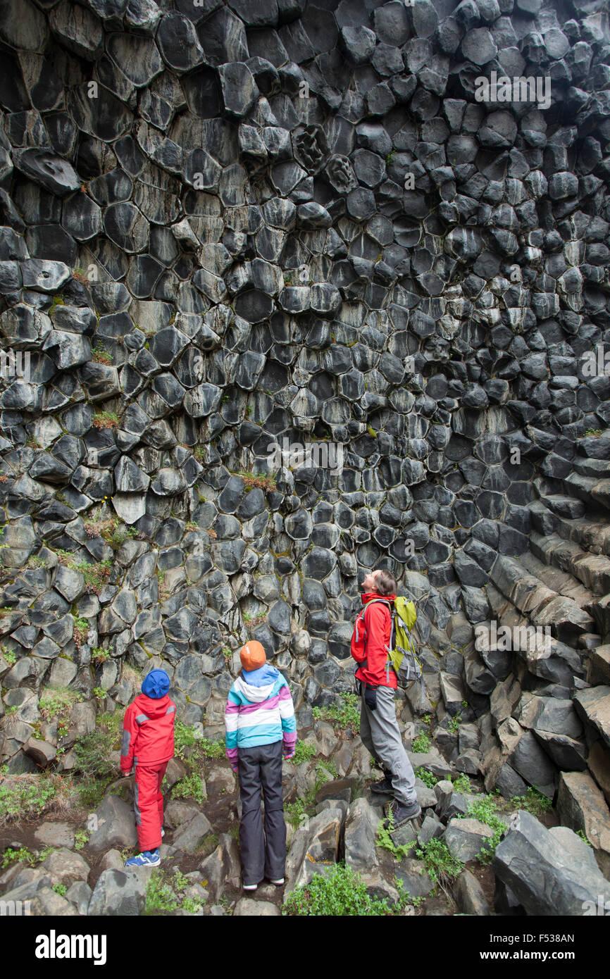Familia estudiando en formaciones de roca basáltica, Jokulsargljufur Hljodaklettar, Nordhurland Eystra, Islandia. Imagen De Stock