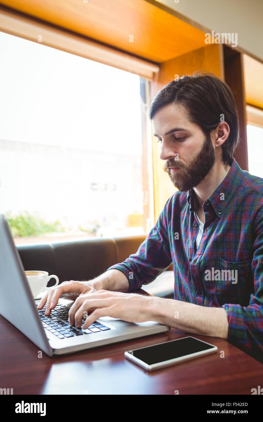 Hipster estudiante usando el portátil en la cantina Foto de stock