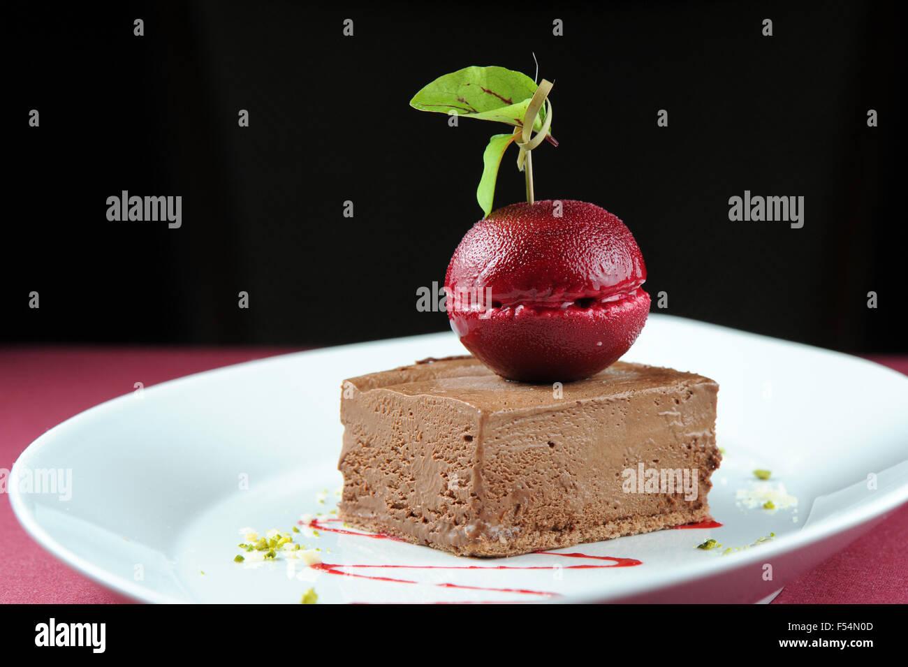 Ratón Chocolate Gourmet postre helado con un sorbete de color cereza oscuro. Imagen De Stock