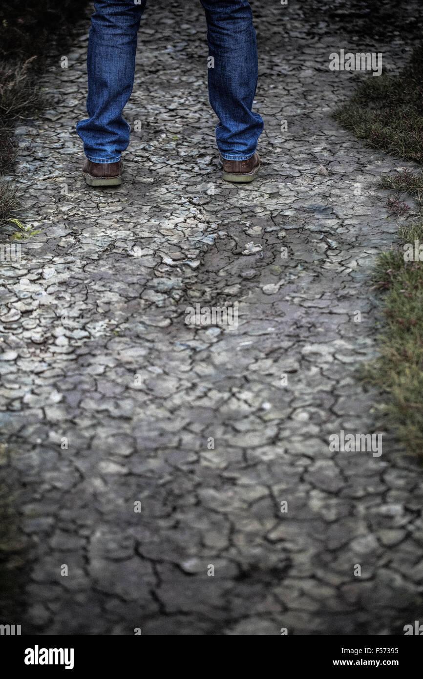 Las piernas del hombre de pie en terrenos agrietados Imagen De Stock