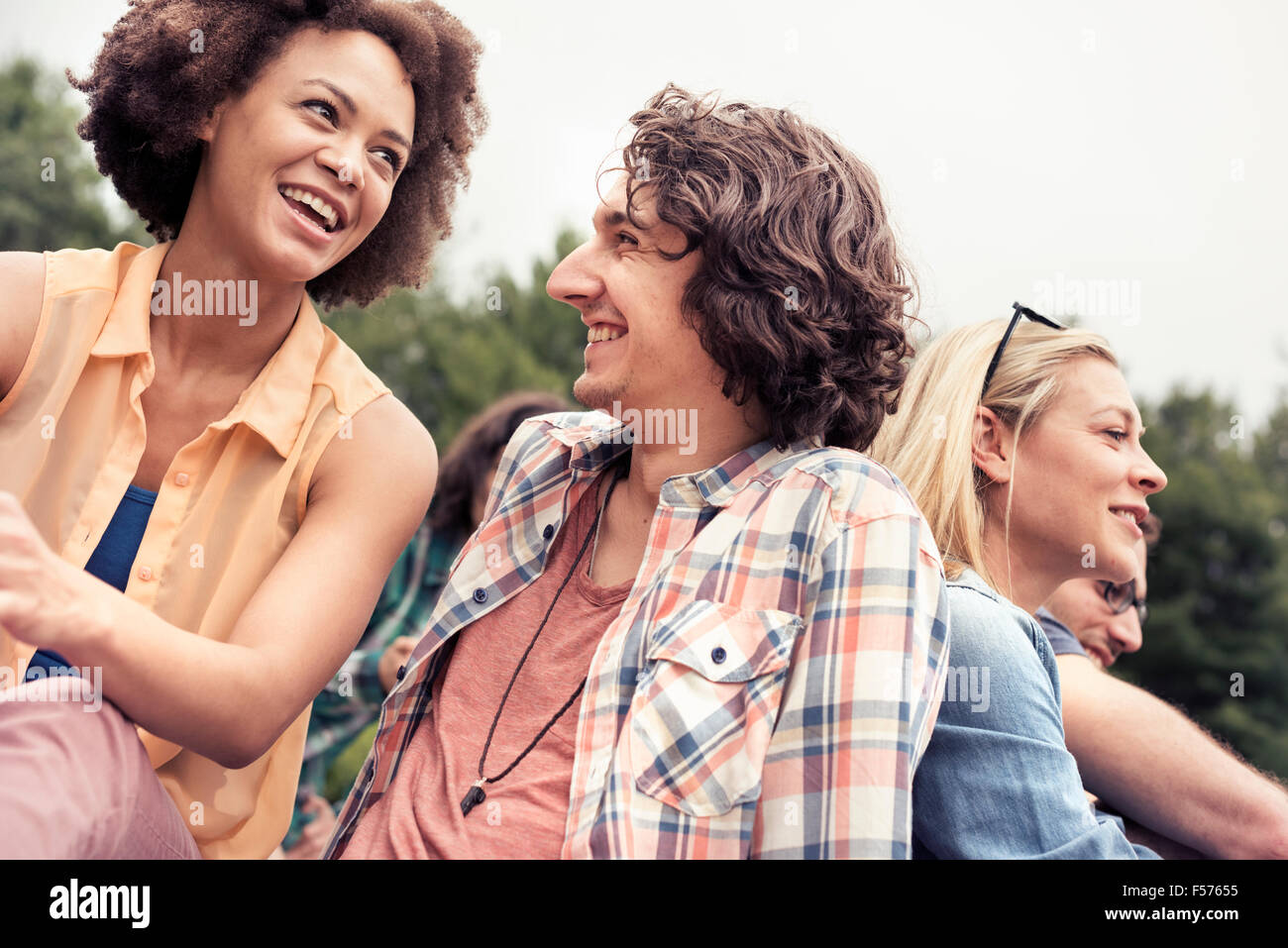 Una joven pareja, un hombre y una mujer, entre otros al aire libre en el campo. Imagen De Stock