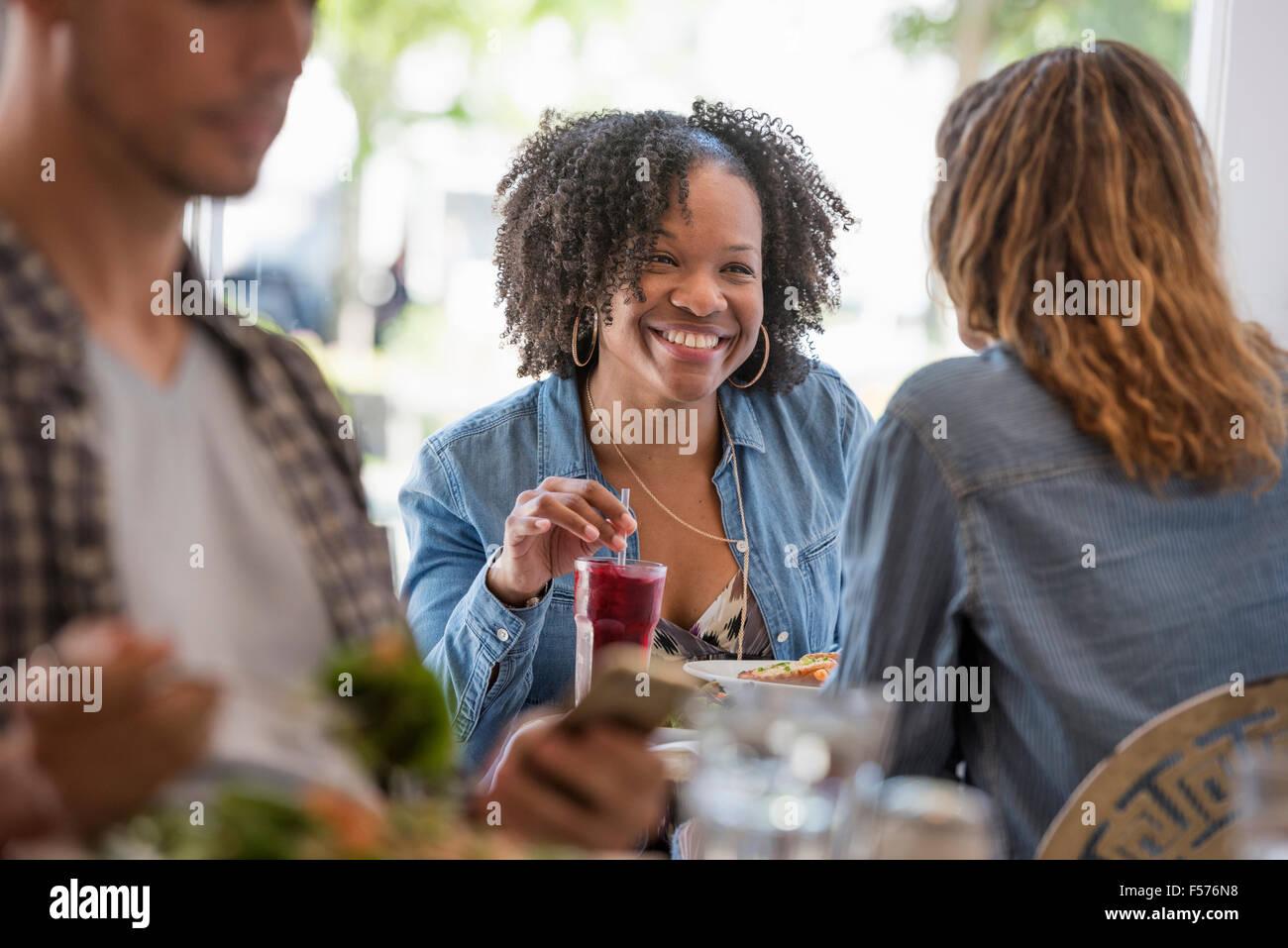 Tres personas sentadas en una mesa en una cafetería. Dos mujeres riendo. Imagen De Stock