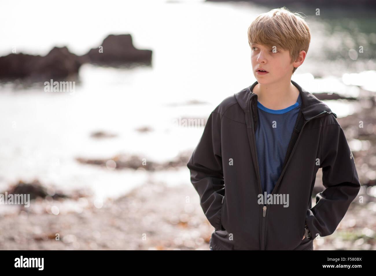 Rubio blanco adolescente en una chaqueta negra camina sola en una playa mirando triste y desgraciada en otoño de sol Foto de stock