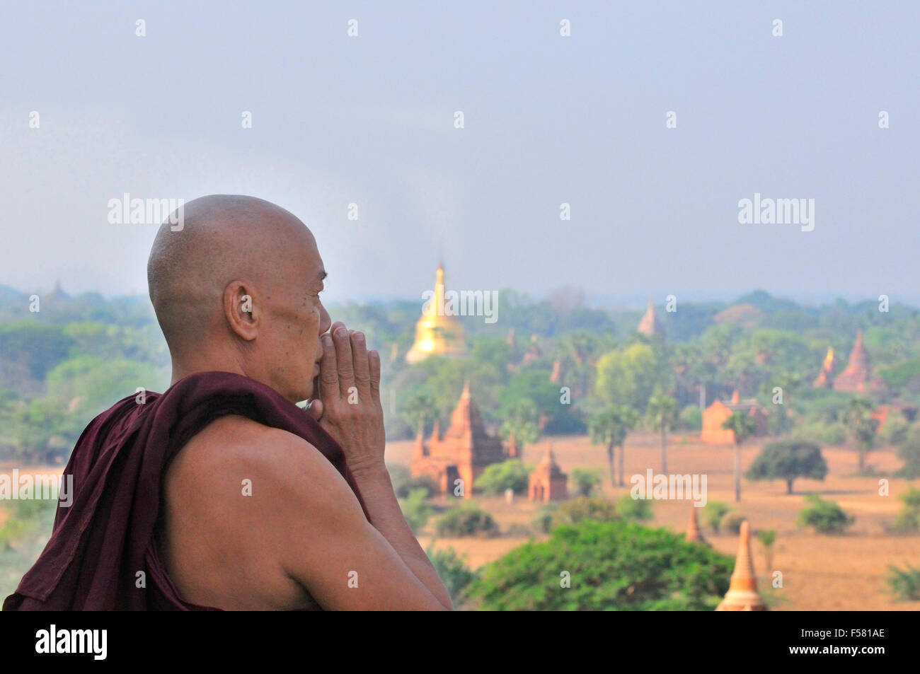Monje budista rezando en la parte superior de la Pagoda Shwesandaw en Bagan, Birmania (Myanmar) Foto de stock