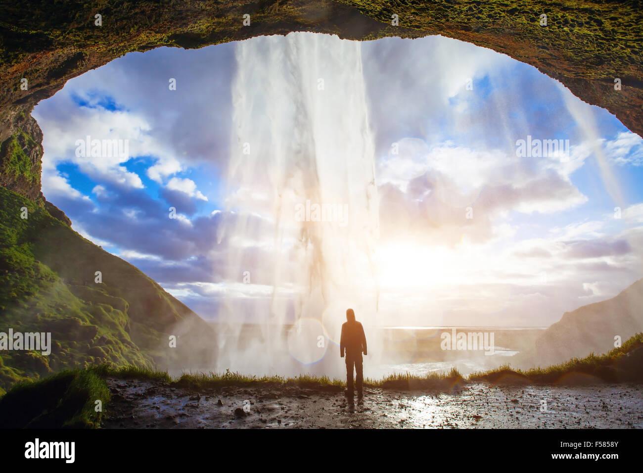 Increíble cascada en Islandia, la silueta del hombre disfrutando de impresionantes vistas de la naturaleza Imagen De Stock