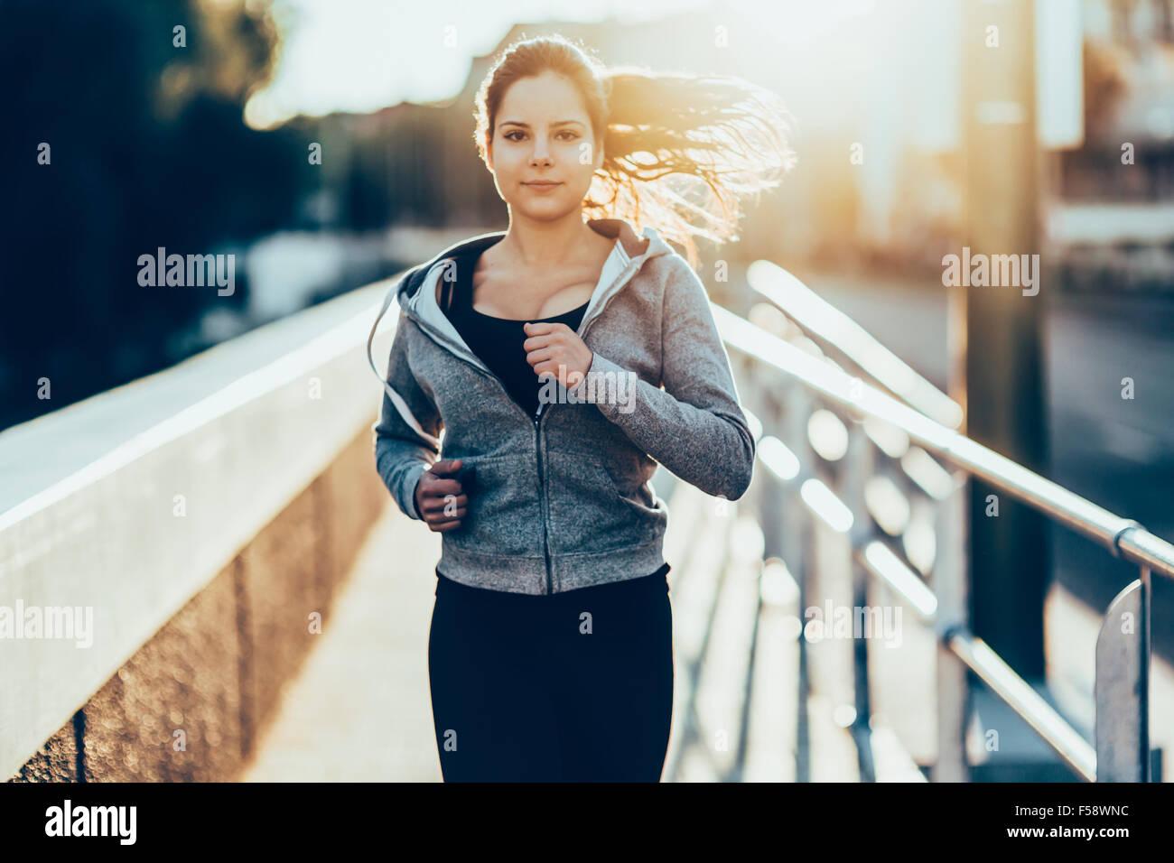 Mujer trotar en la ciudad deportiva para mantener su cuerpo y alma en forma Imagen De Stock