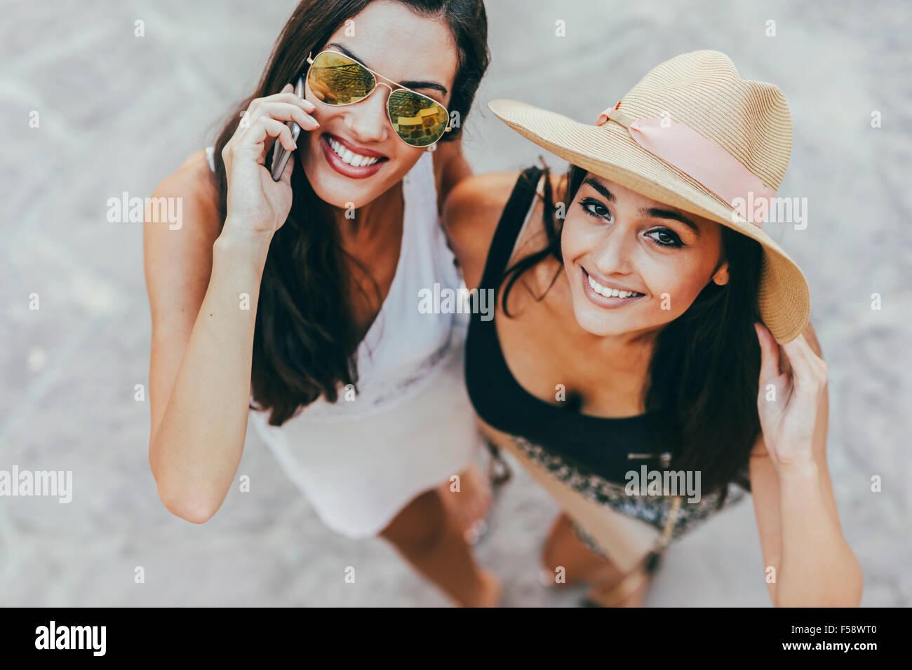 Retrato de dos hermosas chicas en ropa de verano sonriendo y hablando por teléfono Imagen De Stock