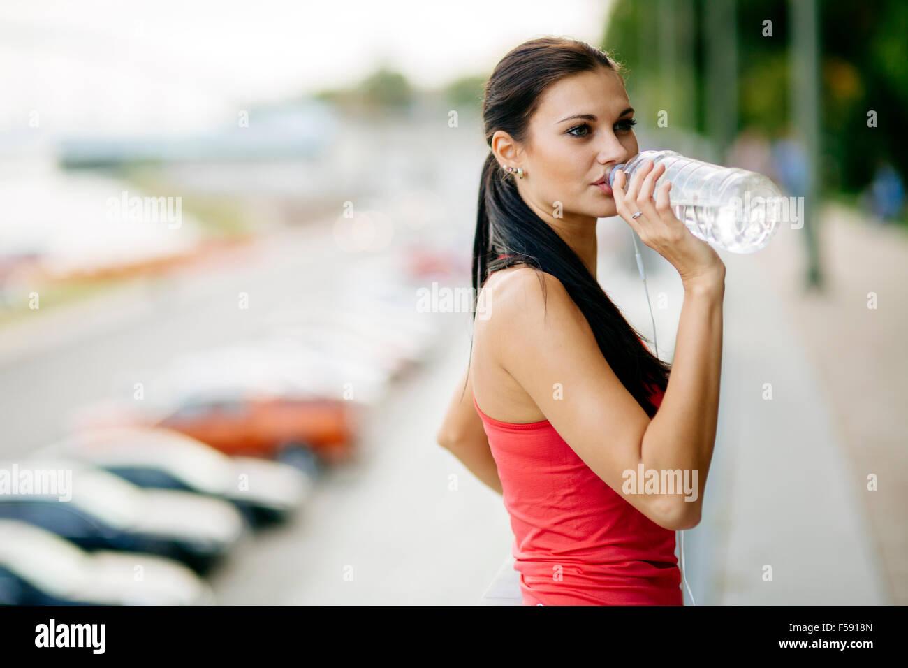 Mujer sedienta de agua potable para recuperarse después de hacer footing Imagen De Stock