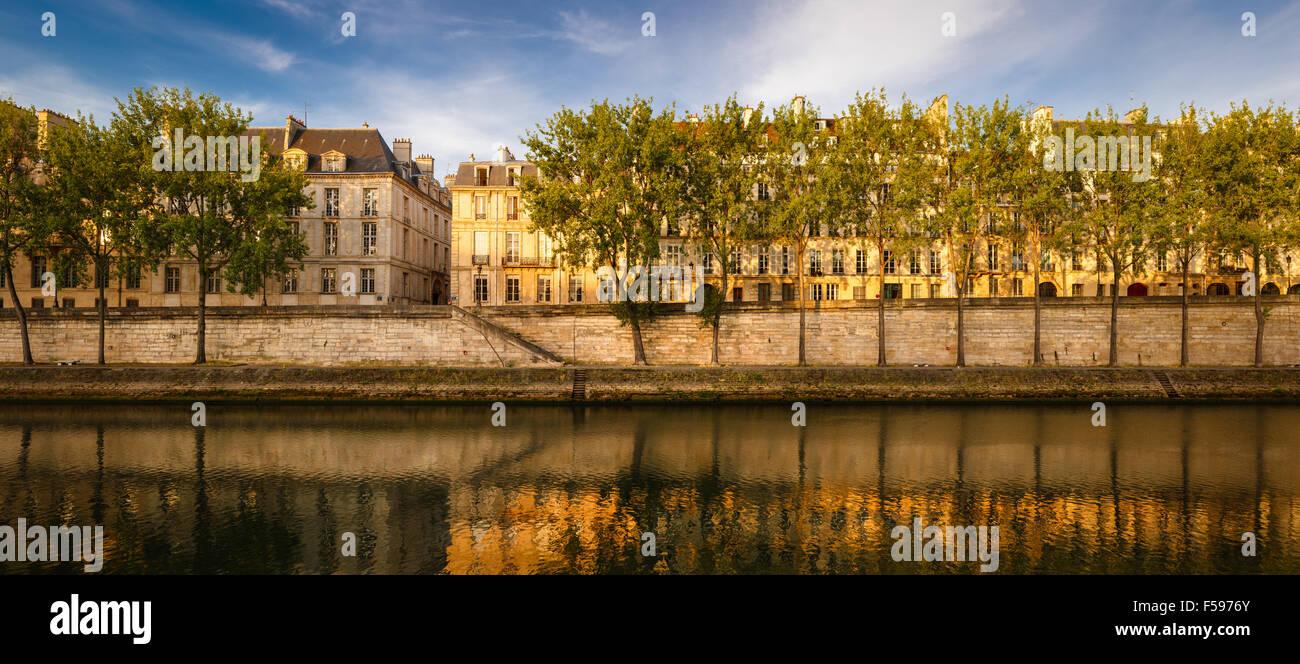 Tranquila mañana de verano en el Aspen arbolado orilla del río Sena. Quai d'Anjou, Ile Saint Louis, París, Francia (75004) Foto de stock