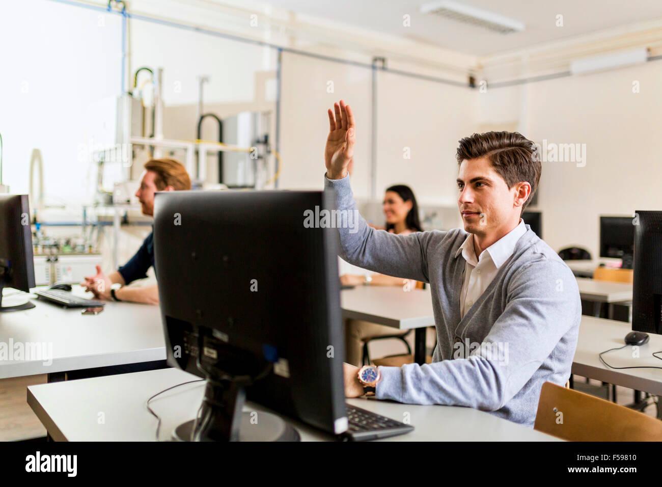 Joven apuesto hombre sentado delante de un PC levantando la mano Imagen De Stock
