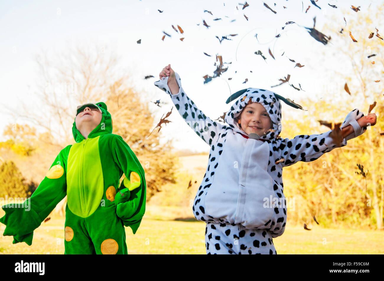 Dos muchachos en traje coger y tirar las hojas Imagen De Stock