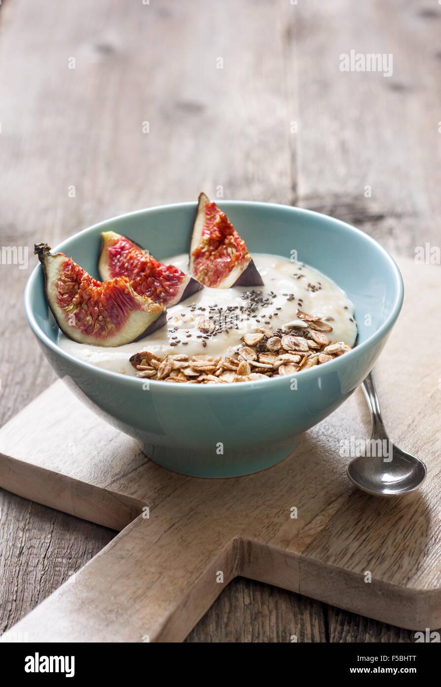 Desayuno con muesli, yogur, higos y chia semillas en un recipiente azul sobre un fondo de madera Imagen De Stock