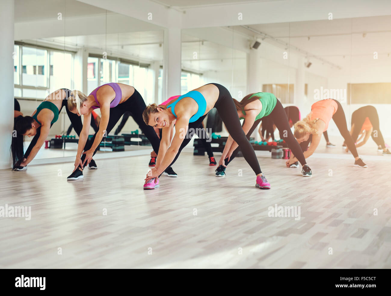 Grupo de mujeres en telas coloridas en un gimnasio haciendo aerobics o el calentamiento con ejercicios de estiramiento Imagen De Stock