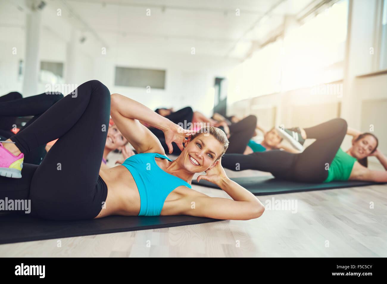 Atractiva mujer joven sonriente haciendo ejercicios aeróbicos en el gimnasio con un grupo de jóvenes en Imagen De Stock