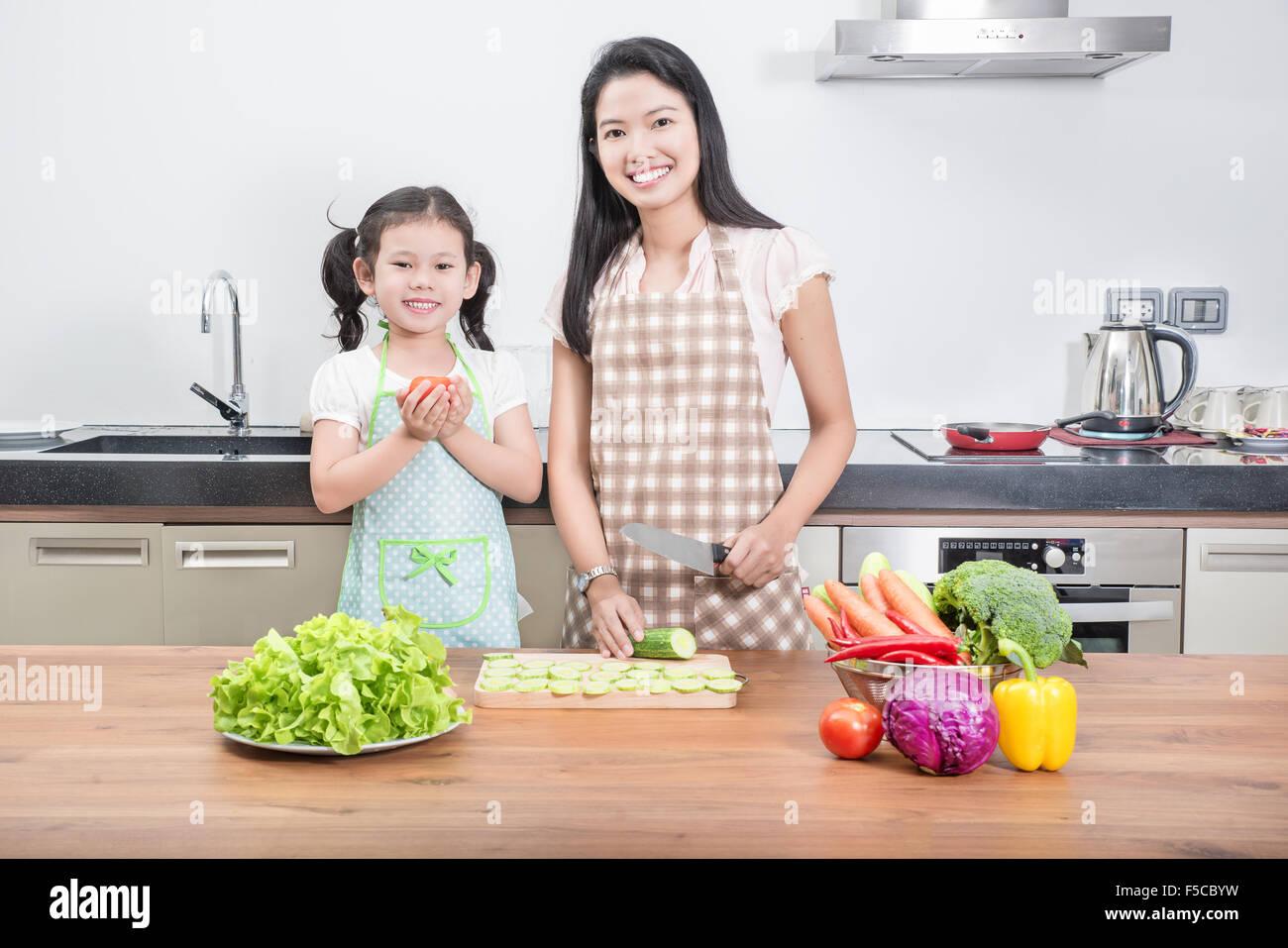 La familia, la infancia y la gente feliz concepto asiático - Madre e hija kid cocinar en la cocina de casa Imagen De Stock