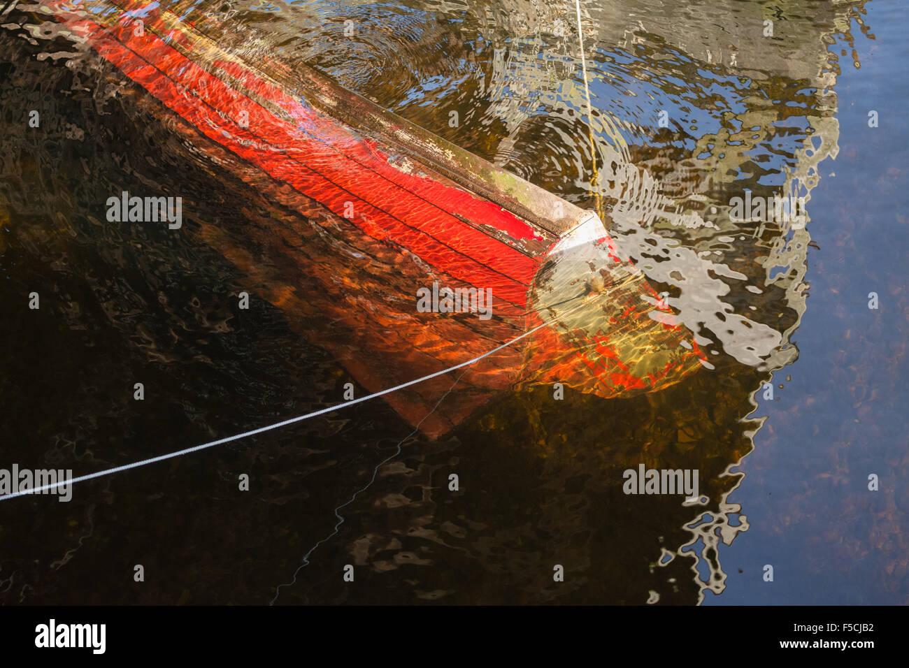 Hundimiento barco - viejo bote a remo de madera roja sumergido bajo el agua. Imagen De Stock