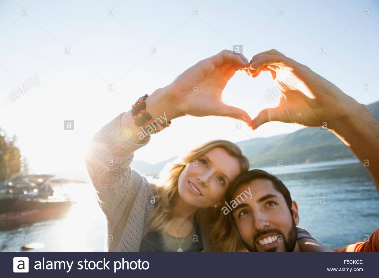 Pareja joven formando forma de corazón con manos lakeside Imagen De Stock