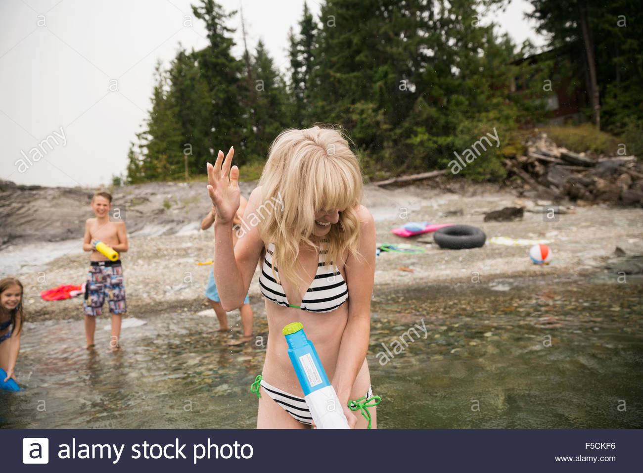 Familia lúdica con pistolas de agua en el lago Imagen De Stock