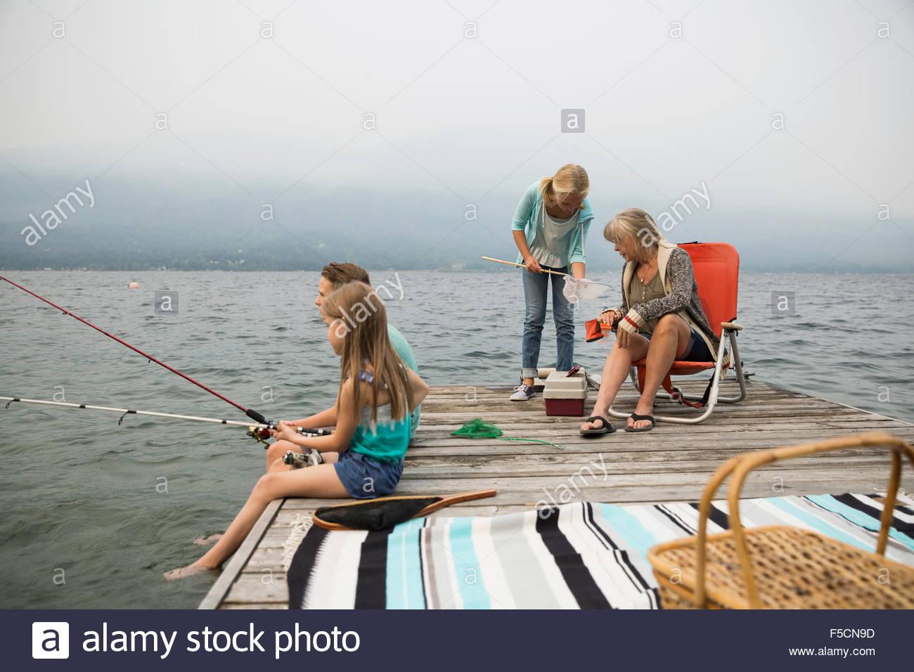 Abuela y nietos de pescar en el lago dock Foto de stock