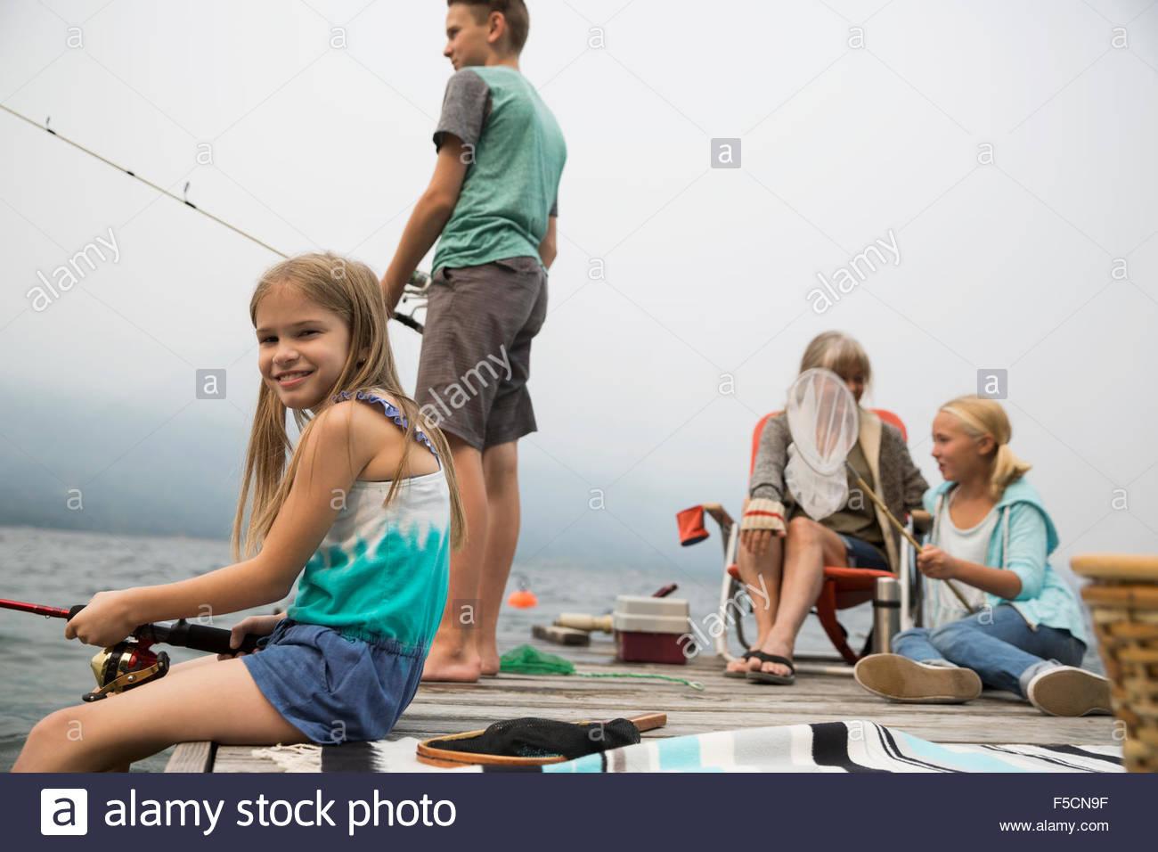 Abuela y nietos de pescar en el lago dock Imagen De Stock