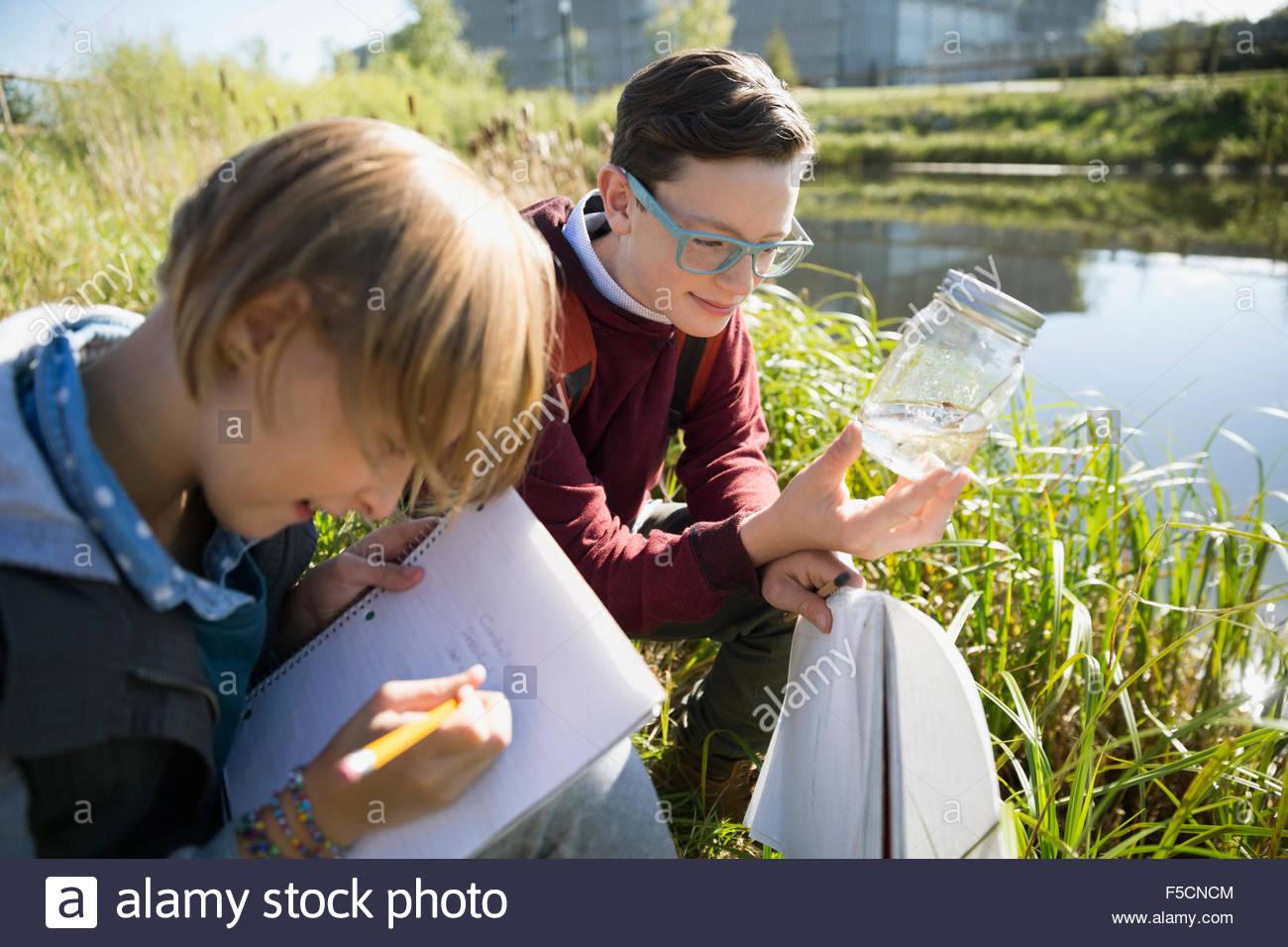 Los estudiantes examinan el agua y tomando notas de viaje de campo Imagen De Stock