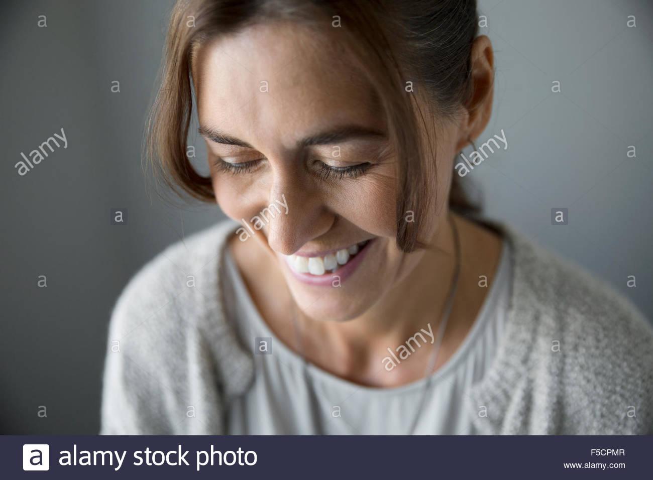 Cerrar hasta risa mujer mirando hacia abajo Imagen De Stock