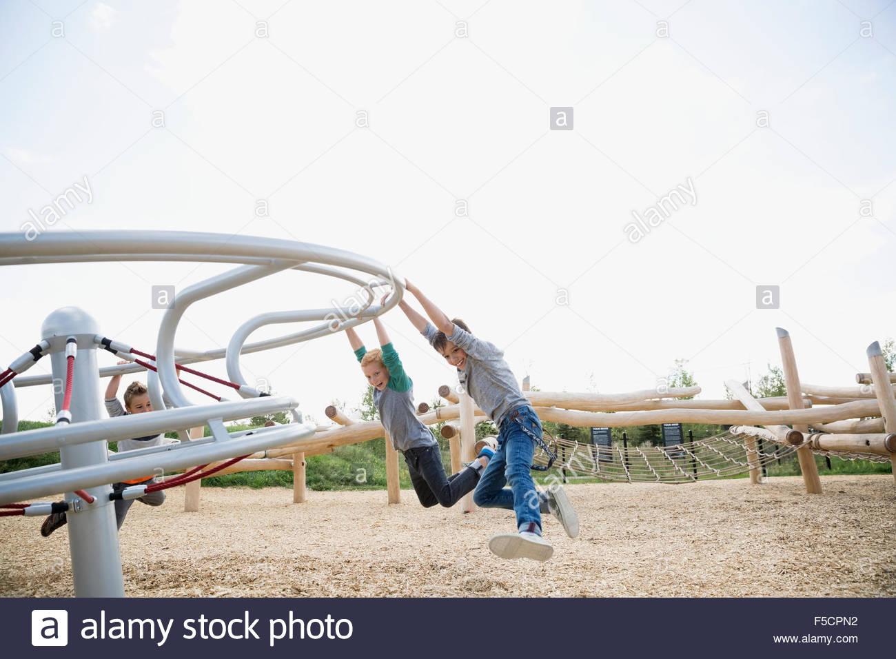 Los niños colgando de barra giratoria en el soleado patio Imagen De Stock