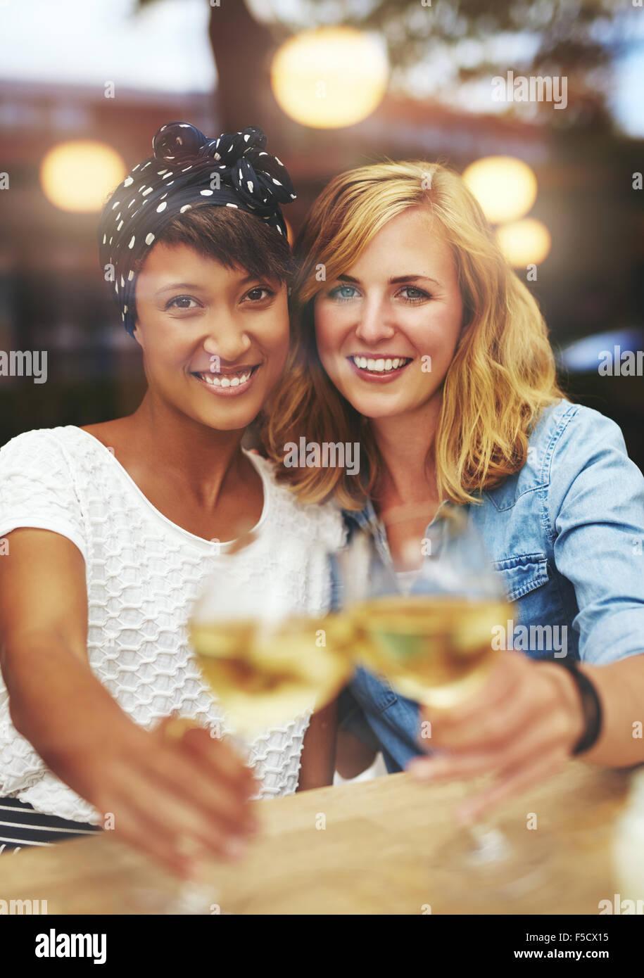 Diversión atractiva amigas jóvenes celebrando con vino blanco tintinea sus copas en un brindis como sonríen Imagen De Stock