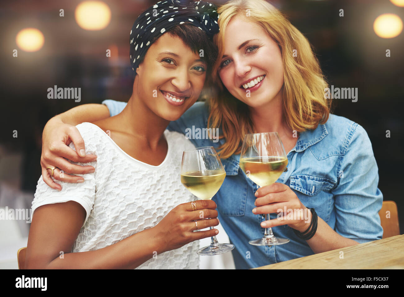 Dos hermosas jóvenes mujeres multiétnicas disfrutando de una copa de vino elevando sus copas en un brindis Imagen De Stock