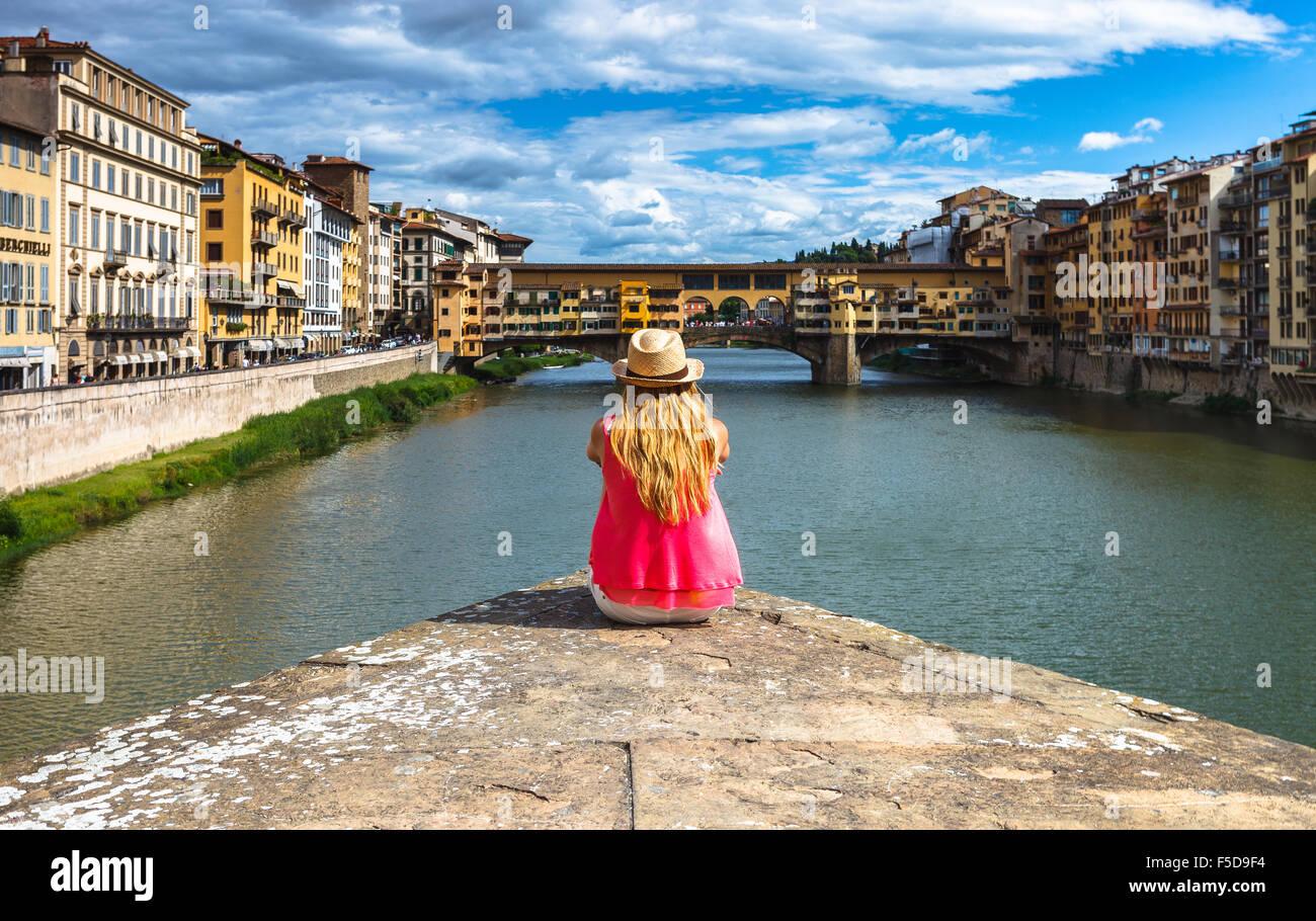 Una joven mujer disfrutando de la vista del Ponte Vecchio y del río Arno, Florencia, Toscana, Italia. Imagen De Stock