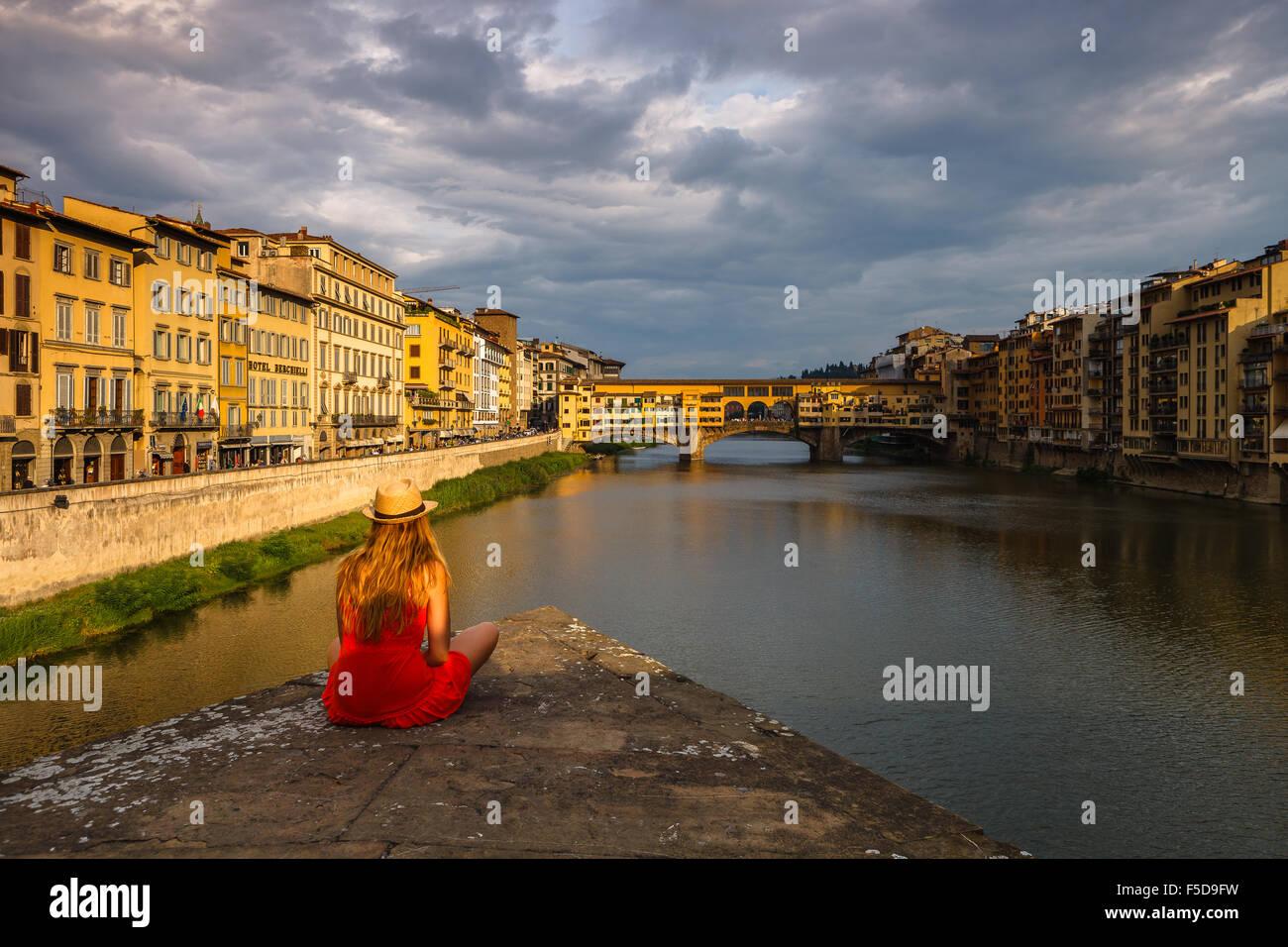 Una joven mujer disfrutando de la vista del Ponte Vecchio y del río Arno, al atardecer, Florencia, Toscana, Imagen De Stock