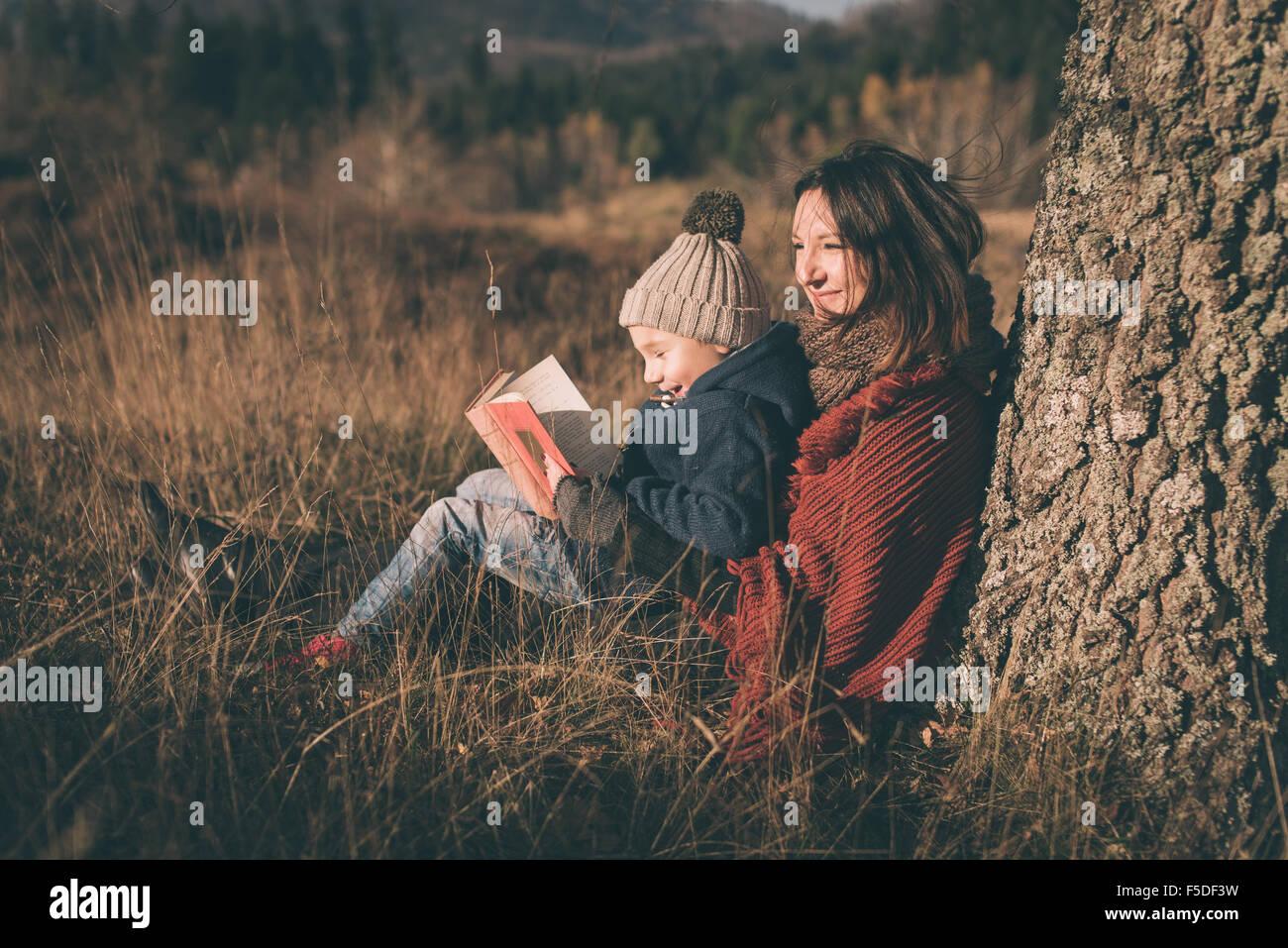 Madre e hijo en la naturaleza. Libro de lectura y sonriente. Foto de stock
