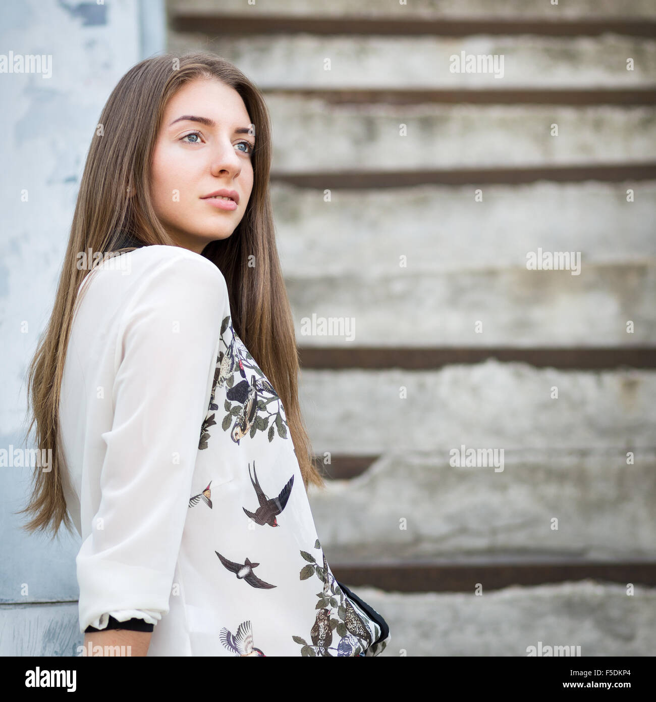 Hermosa niña adulta de pie en las escaleras y mirando directamente Imagen De Stock