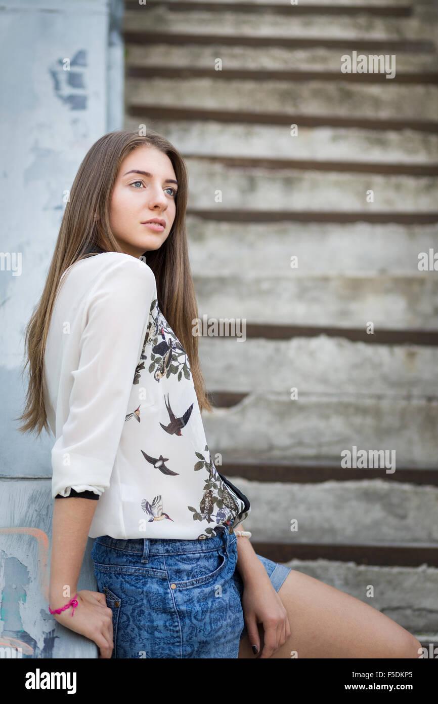 Los jóvenes caucásicos hipster chica relajante en las escaleras de la ciudad. Imagen De Stock
