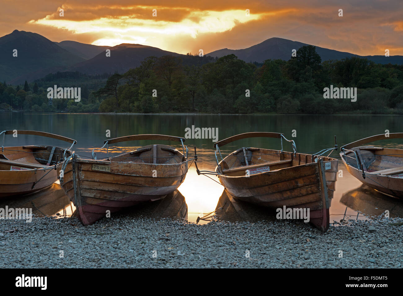 Barcas de remos en la orilla del agua Derwent al atardecer cerca de Keswick, Cumbria, Lake District, Inglaterra, Imagen De Stock