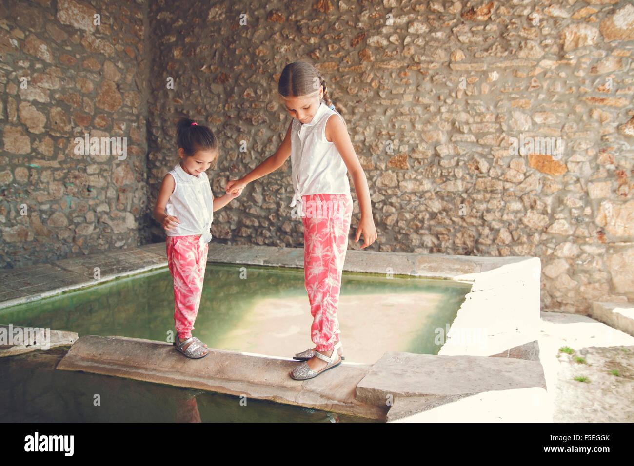 Dos chicas caminando por cornisa por una piscina de agua Imagen De Stock
